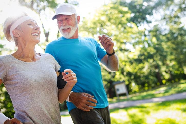 happy elderly couple exercising outside