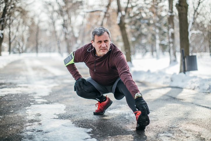 elderly man stretching during winter