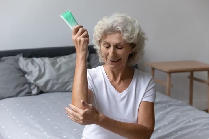 elderly woman holding elbow
