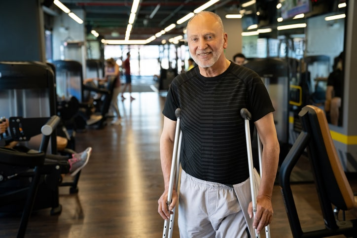 elderly man on crutches at the gym