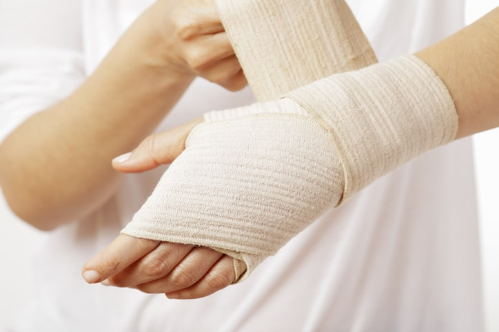 person wrapping wrist with bandage